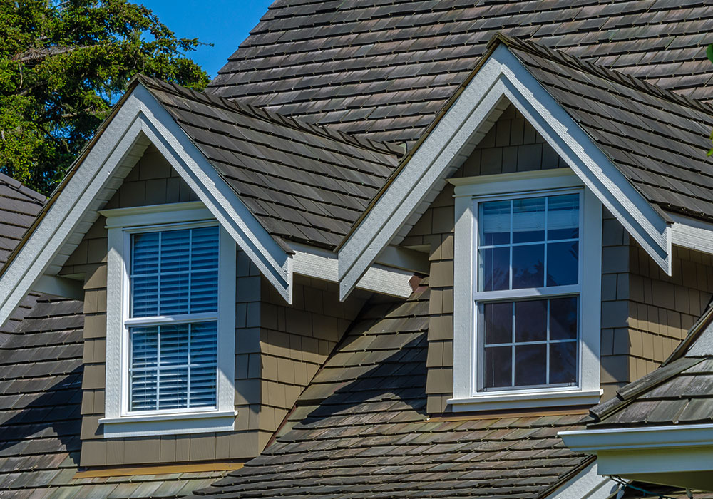 Aesthetically pleasing, exterior windows on the upper level of a beautiful house with wood shake shingles