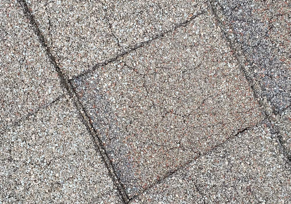 Old, cracked, weathered shingles that are in desperate need of being replaced