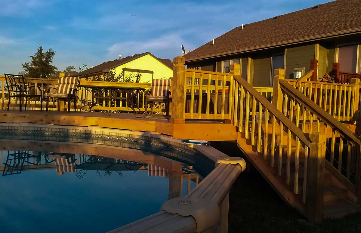 Check out this cedar deck that is partially wrapped around this swimming pool